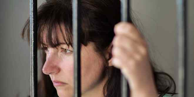 The girl is imprisoned in jail, behind bars.
