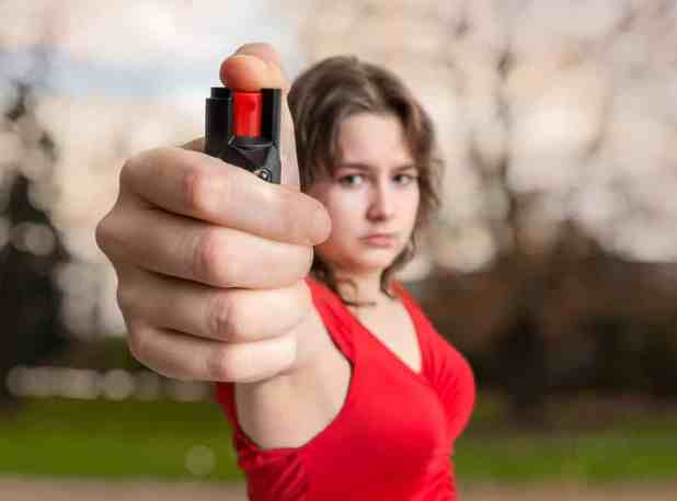 Self-defense concept. Young woman holds pepper spray in hand.