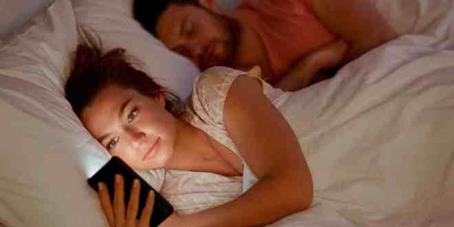 woman using smartphone at night while her boyfriend is sleeping