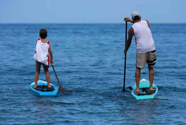 Little boy and young father, enjoying stand up paddle boarding,
