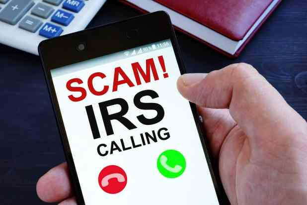 Hand is holding phone with irs scam calls.