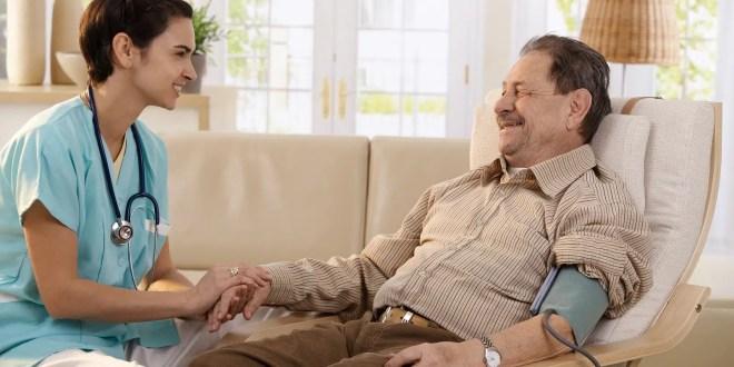 Nurse measuring blood pressure of senior man at home
