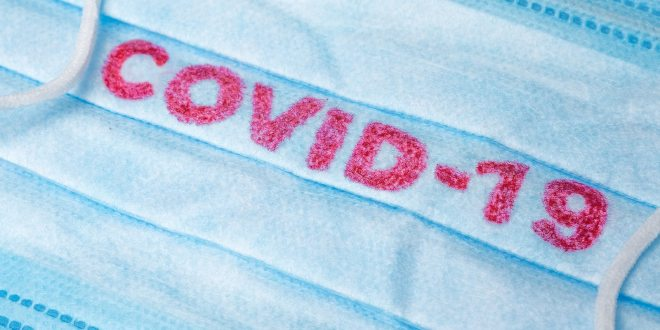 Disposable Face Mask with covid-19 printed on it.