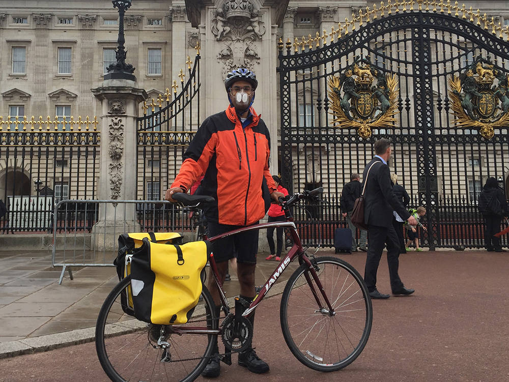 Dr. Anil Simhadri with his Totobobo mask and bicycle in front of the Birmingham Palace in London