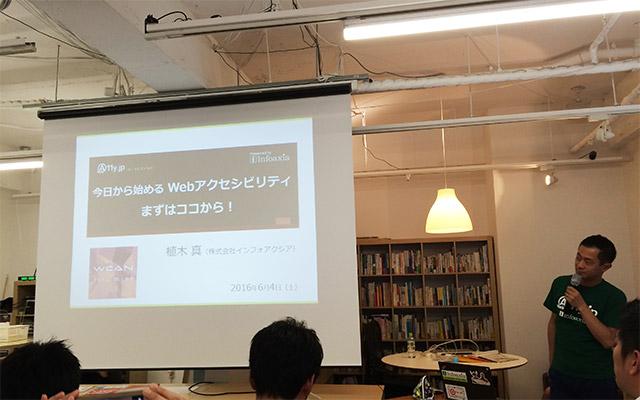 写真:セッション前の撮影タイムでスライドの映るスクリーンと植木さん