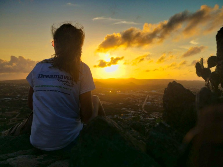Representing travel agency Dreamavoo Travel & Tours during the sunrise at the peak of Hooiberg in Aruba, for Ellen Blazer's travel blog To Travel and Bloom