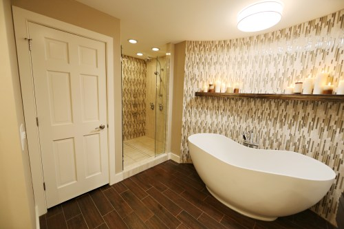 Bathcrashers bath tiled with wood plank floor tile, schluter systems linear drain, and curved mosaic accent wall.