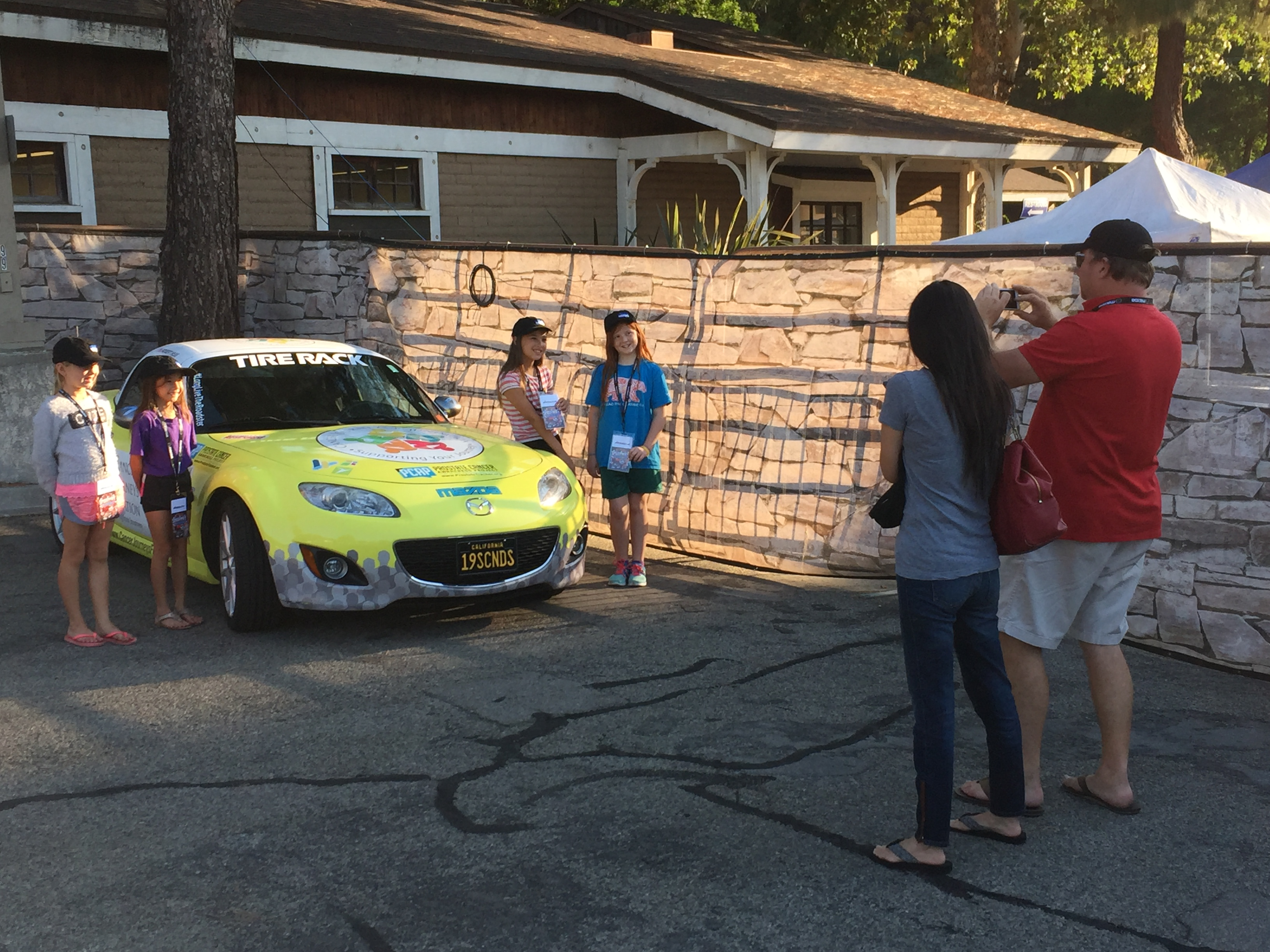 family taking a picture of the Cancer Journeys Foundation MX-5 Miata
