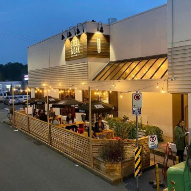 An outdoor brewery patio at evening with lights