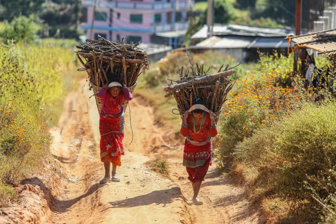 woman in red dresses carrying firewood ethical tourism
