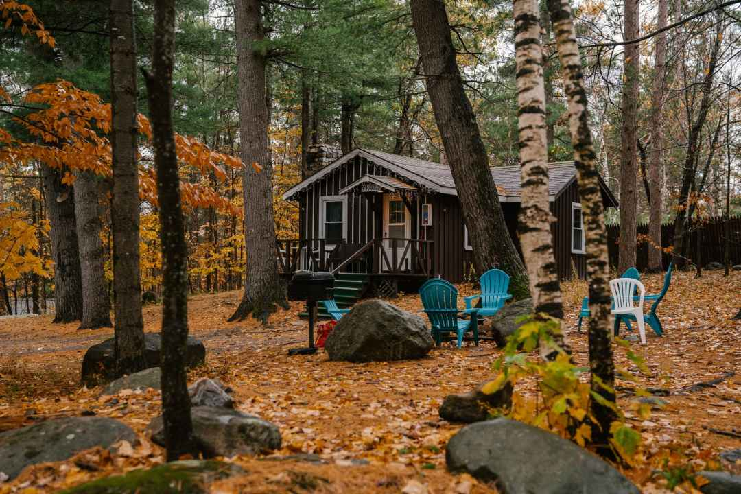 cozy wooden house and chairs in autumn forest ethical tourism