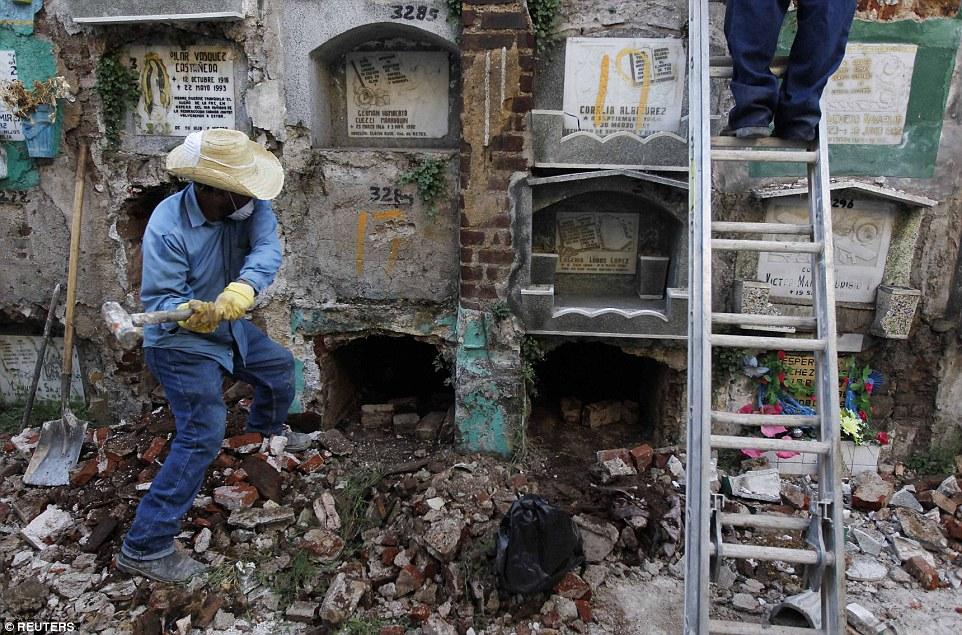 могильщик разрушает стену склепа
