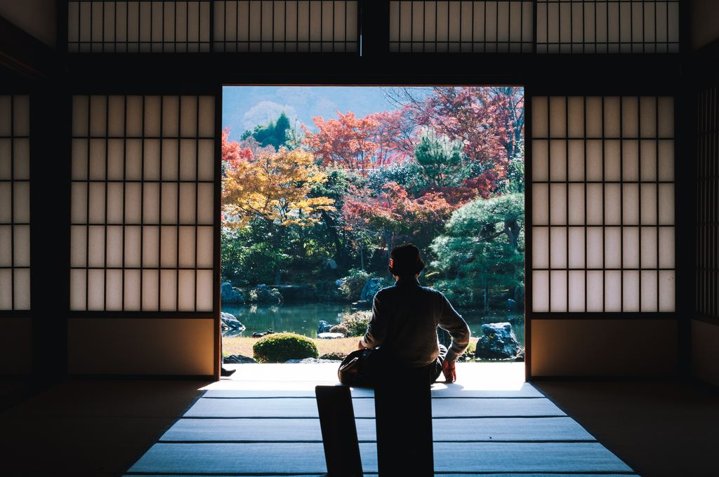 Man looking out of traditional Japanese house in Kyoto, Japan