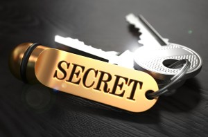 Keys and Golden Keyring with the Word Secret over Black Wooden Table with Blur Effect.