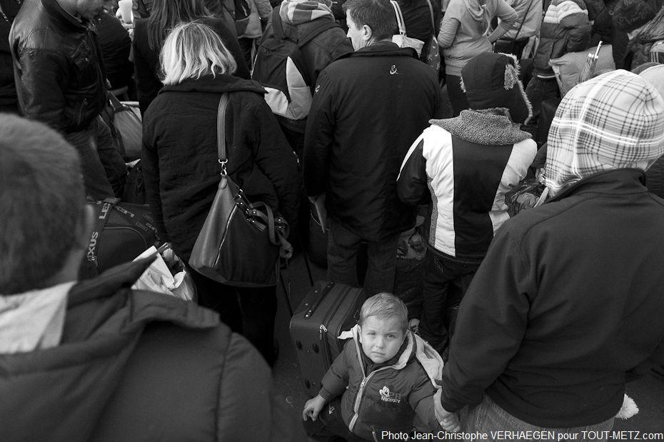 Les familles attendent pour charger les soutes des bus avec leurs bagages plus réduits que prévu. Nul ne sait quel sera le parcours de cet enfant.