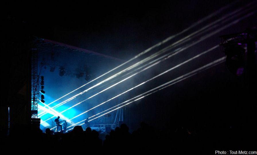 Le parc de la Seille est plongé dans la pénombre. C'est au tour d'un groupe electro-rock de monter sur scène. Il assurera l'animation musicale du spectacle aérien qui se profile.