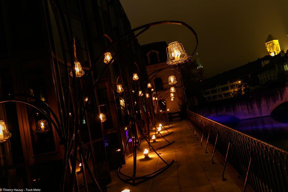 Vers la droite du bâtiment du Conseil Général, une allée peuplée de nouvelles lanternes invite à longer l'autre bras mort de la Moselle. Ces lanternes là sont en verre et ont été soufflées à Meisenthal.