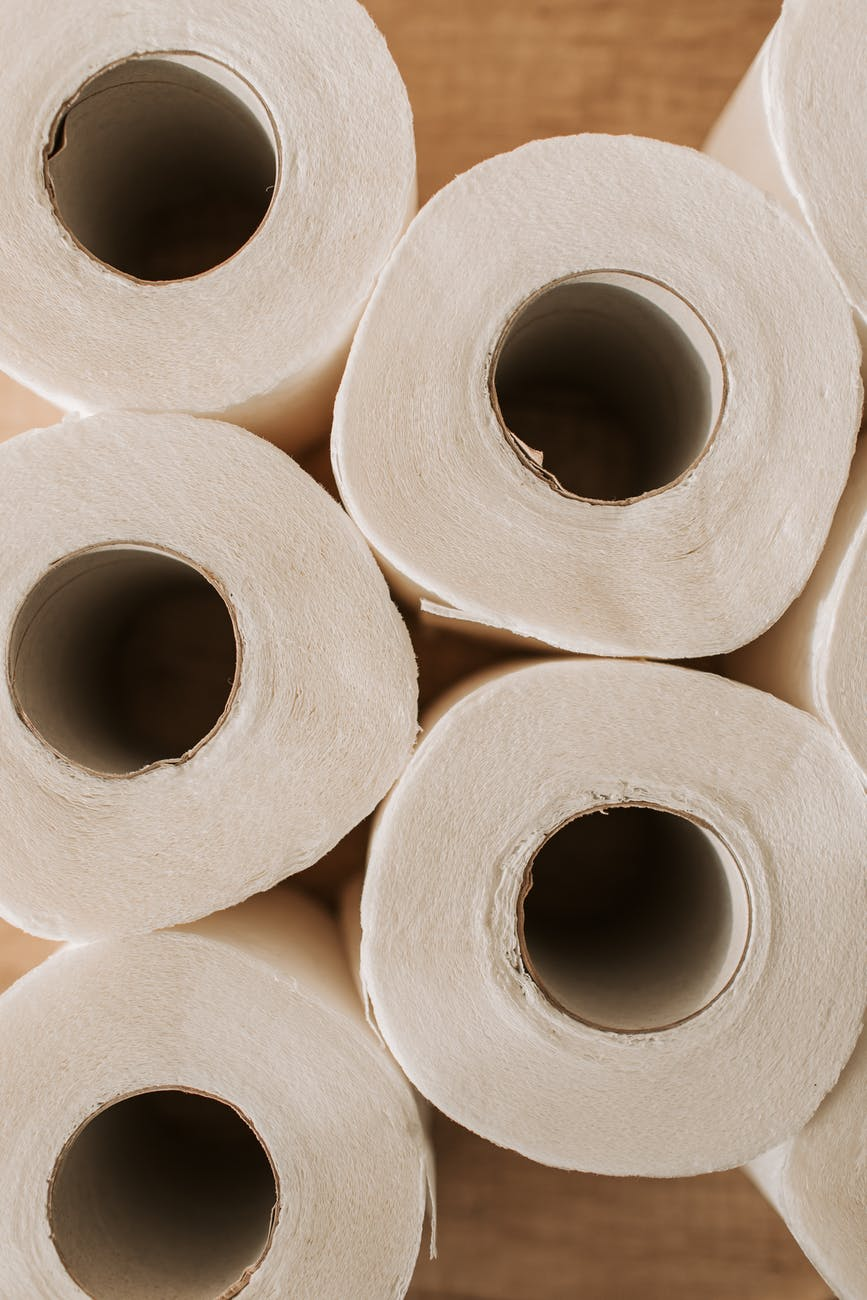 set of toilet paper on wooden background