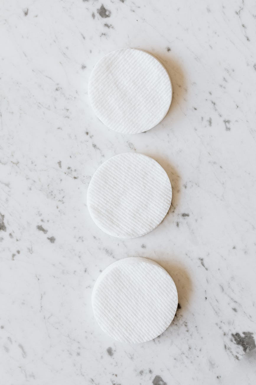 identical round shaped cotton pads on marble surface