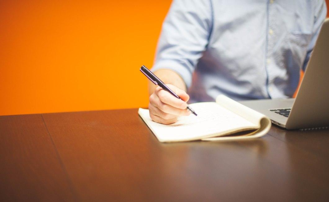 Person, der skriver - måske i færd med at besvare følsomme spørgsmål.