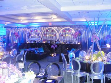event production with clear acrylic chairs and black tables