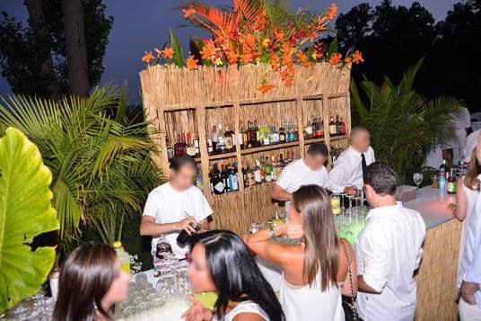 Corporate-event-with-tiki-Bar-with-palm-trees-bartenders-and-crowd-ordering-drinks