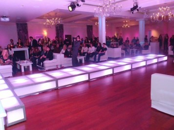 LED-stage-deck-runway-with-event-furniture-and-audience