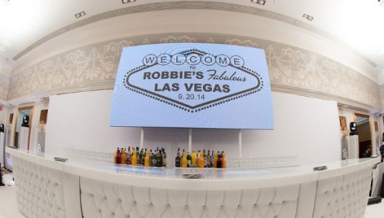 White-full-tufted-bar-with-giant-video-screen-Vegas-sign