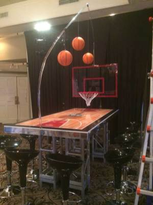 Basketball-Mitzvah-basketball-court-table-with-black-scoop-stools-and-basketball-hoop