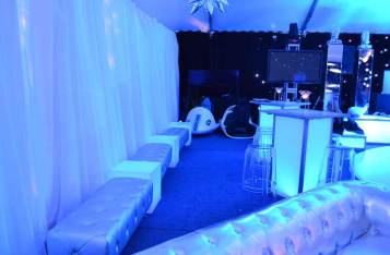 space theme bar mitzvah event with silver bench furniture, pipe and drape, and illuminated hi-boy tables
