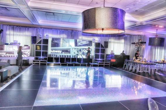Holgraphic-dance-floor-with-giant-shade-chandeliers-and-white-lounge-decor