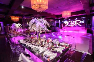 Bat-mitvah--event-decor-white-dance-floor-community-tables-with-centerpieces