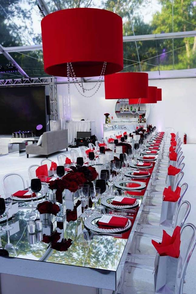 mirrored-community-table-ghost-chairs-red-canvas-chandeliers-black-china-floral-centerpieces-for-sweet-sixteen