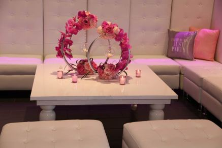 Event-furniture-white-hi-back-couches-white-laquer-table-pink-rose-and-silver-centerpiece-and-candle-holder