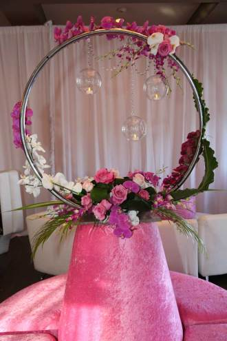 Pink-borne-couch-with-big-silver-circle-pink-flowers-and-crystal-balls-holding-candles