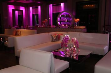 White-lounge-furniture-with-mirrored-tables-tufted-bar-and-custom-lighting