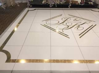 Portable-white-matte-dancefloor-with-shiny-gold-border-and-monogram