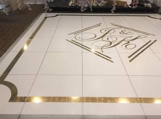 Portable-white-matte-dancefloor-with-shiny-gold-border-and-monogram