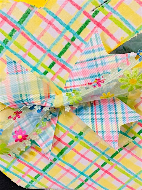 Reversible Wooden Fabric Decoupaged Bunny. It has green circles on one side and pink, yellow, green, blue plaid on the other side. Both sides have matching bows.