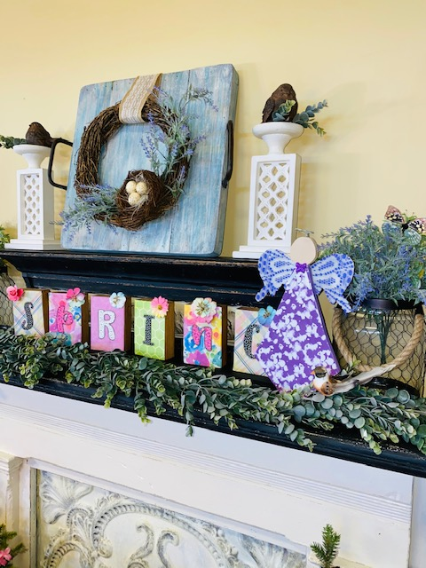 Shades of purple, wooden angel with lace and fabric decoupage. Picture is on top of a fireplace mantel mixed in with other Spring Decor.