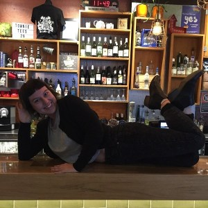 Staff member posing on the bar of the Town Hall Hotel Newtown