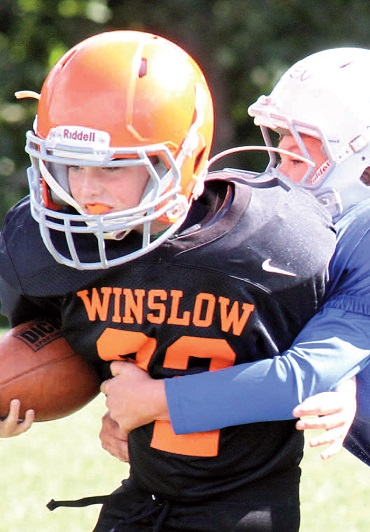 Winslow third/fourth grade youth football team member Ethan McCaslin runs with the ball while Messalonskee youth team member Owen Kirk goes for the tackle during a recent game.  Photos by Mark Huard, owner Central Maine Photography