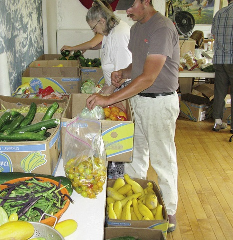 Volunteers Peter Nerber Jr., right, and Marina Grant, sorting vegetables for the food pantry. Below, members of the Great ThunderChicken Drum. The drum meets every Tuesday evening from 7 - 9 p.m. and is open to all. Photo by Connie Bellet