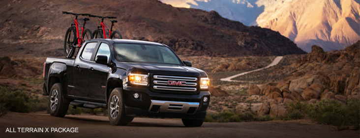 Image of the 2017 GMC Canyon All Terrain X driving on a mountain rode with two bicycles in the bed.