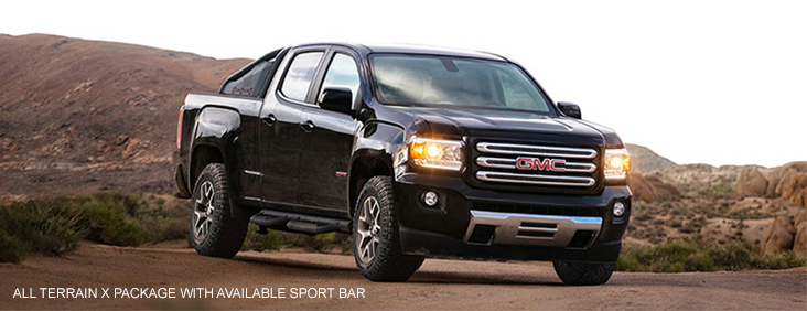 Image of the 2017 GMC Canyon All Terrain X with available sport bar driving on a dirt road.