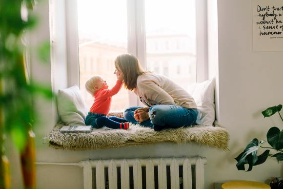 Mother and toddler interact with each other on a window seat. The best toys promote positive feelings.