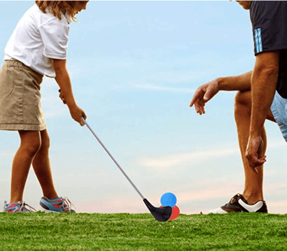 Father teaching his young daughter to plat golf. This is a great outdoor activity for encouraging more physical exercise.