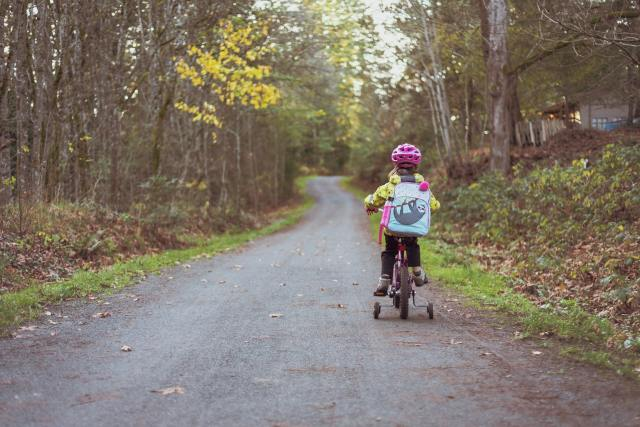 Girl riding a bike with training wheels at Easter. Active gift for a child 3 to 5 years old.