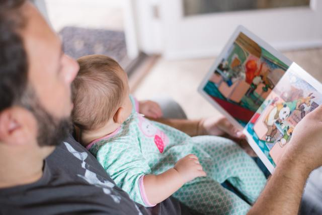 Father reading a picture book to a baby. This is the most effective method of teaching the joy of reading.