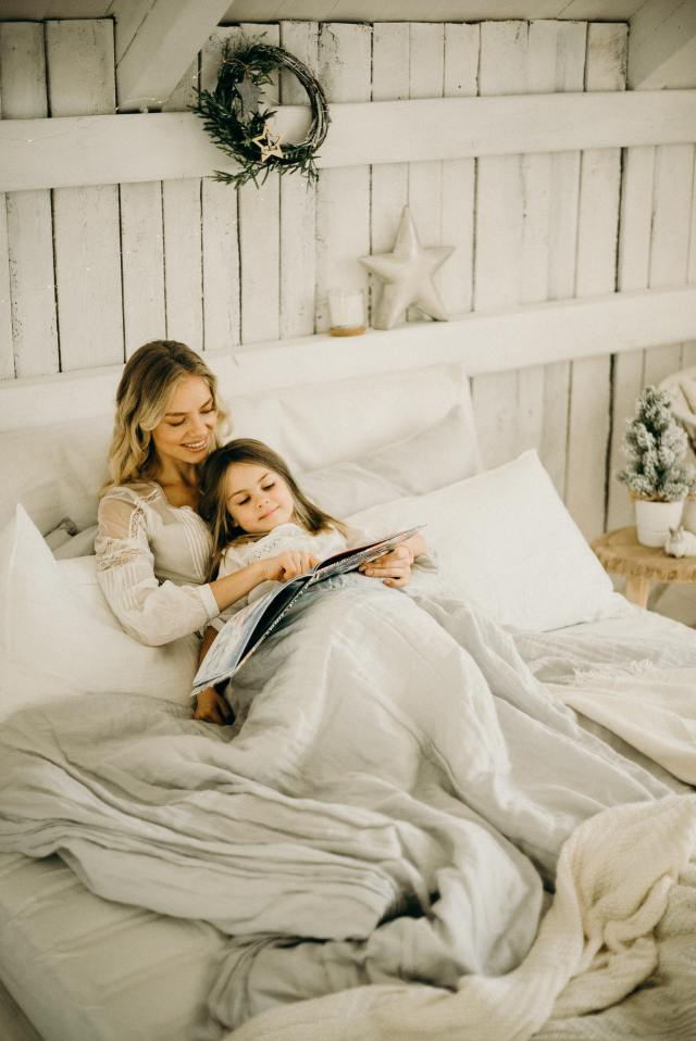 Mother reading a storybook to her daughter to reduce emotional distress such as controlling her anger, being jealous of the new baby.